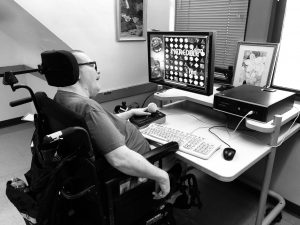 Man sits in a power wheelchair using an adaptive mouse at a desktop computer.
