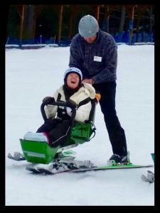 Candace rides her bi-ski through the snow with her instructor behind her, head tilted back, laughing with joy.
