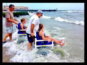 Ciara rides a beach wheelchair into the waves with her head tilted back with joy next to her sister who is also using a beach wheelchair. A man pushes each woman's chair.