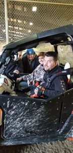 Daniel smiles from a mud splattered two seater utility vehicle with his hands on hand controls. A man sits next to him and two other men lean in smiling from the far window.