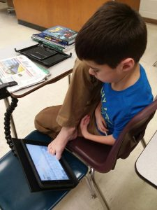 A boy sits in a classroom chair looking down at an iPad that he operates with his toes. The iPad is attached to his desk by a clamp.