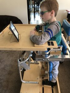 Boy stands in a wooden dynamic stander with his arms resting on the table in front of him while gazing at an iPad that is propped up using the wire from a coat hanger.