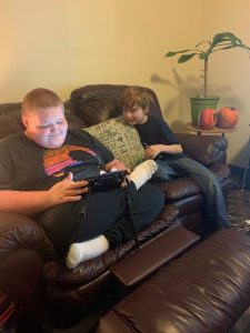 Two boys sit on a couch. One is holding a tablet and the other is looking over his shoulder at the screen.