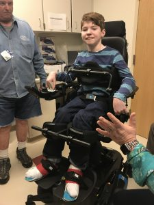 A boy smiles while standing in a standing power wheelchair.