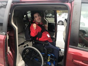 A man smiles from his power wheelchair inside his adapted van.