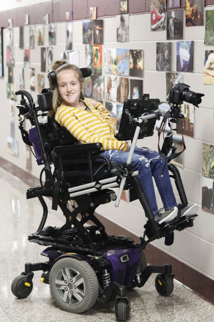 A woman smiles from her power wheelchair with her communication device and camera each propped up in front of her on a stand attached to her wheelchair.