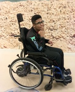 A young man smiles while showing his watch on his wrist and sitting in his manual wheelchair that has a small motorized wheel attached to the back.