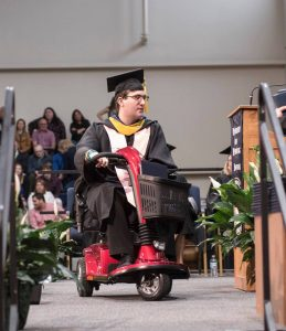 Tyler rides his mobility scooter down an auditorium aisle wearing his graduation cap and gown.