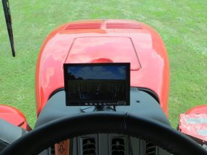 Cab camera set up on the dash of a tractor showing a view of the field behind the tractor