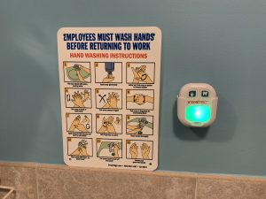 An infographic with details on how to thoroughly wash hands is posted on a bathroom wall next to a timer that lights up for 20 seconds while you wash your hands.