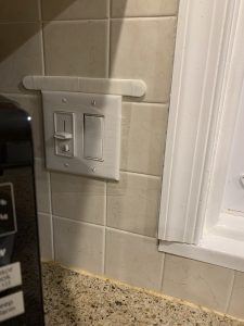 A switch on a tiled kitchen wall is covered in clear plastic, attached to the wall with removable picture-hanging strips.