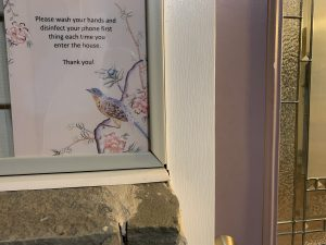 A sign by a front door reads Please wash your hands and disinfect your phone first thing each time you enter the house. Thank you!