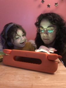 A young girl and her mom huddle over a tablet.