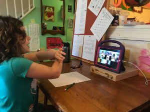 A girl talks with her hands to her classmates through video chat on her tablet screen at a desk.