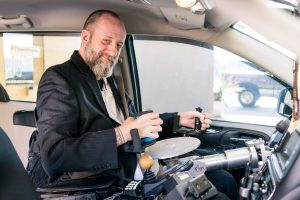 A man smiles from the drivers seat of a vehicle with his hands gripping hand controls.