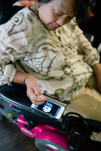 A woman seated in a power wheelchair looks down at her smart phone mounted on the arm of her chair.