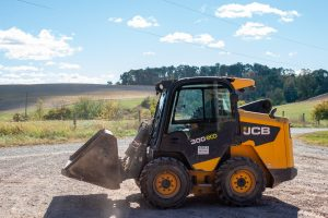 Garvin drives his skid steer across a gravel lot with rolling farmland in the background.