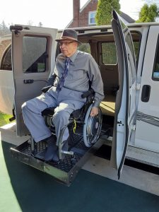An older man using a manual wheelchair rids a lift to exit an adapted van.