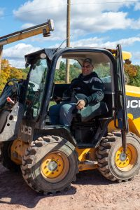 A man smiles while seated in a side-entry skid steer.
