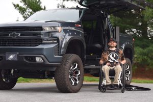 A man seated in a manual wheelchair next to an adapted truck with a lift.