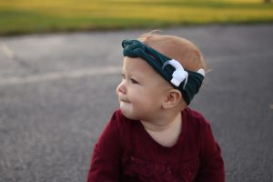 A toddler wears a green headband wrap and a cochlear implant is visible above her ear.