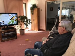 An older man sits in an easy chair watching a football game