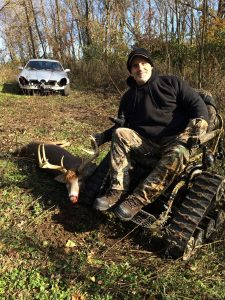 A man poses in an action track chair next to a large buck he shot.