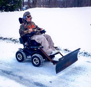 Man rides all terrain power wheelchair with snowplow attached through the snow.