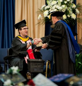 A young man wearing graduation cap and gown receives his diploma while riding his mobility scooter.