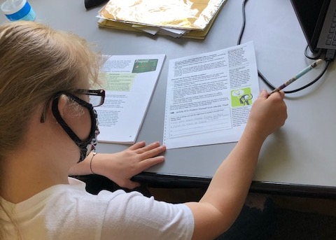 A young woman wearing glasses and a face mask leans over a desk with a pencil in hand, looking at a worksheet.